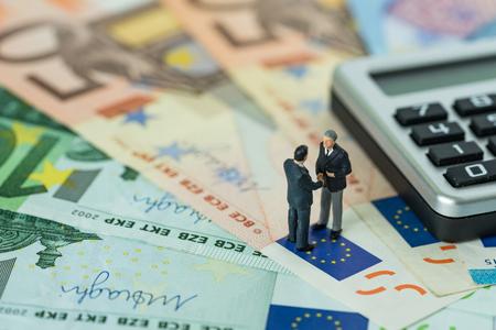 Foto de Miniature figure, businessmen shaking hand standing on pile of Euro banknotes with calculator as Euro economy agreement or Brexit negotiation concept. - Imagen libre de derechos
