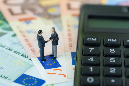Photo for Miniature figure, businessmen shaking hand standing on pile of Euro banknotes with calculator as Euro economy agreement or Brexit negotiation concept. - Royalty Free Image