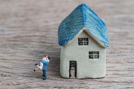 Photo pour Miniature couple, happiness husband and wife with ceramic house using as success marriage life or mortgage concept. - image libre de droit