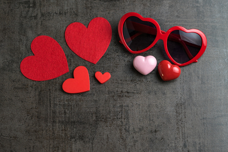 Foto de Red and pink heart shapes with heart shape eyeglasses on black cement wallpaper as Valentine's day concept with copy space. - Imagen libre de derechos