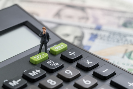 Foto de Miniature people business man thinking and standing with TAX minus button on calculator with background of blurred US Dollar banknotes, United States government tax overhaul, cuts or reduce concept. - Imagen libre de derechos