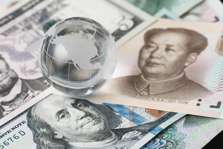 Foto de US and China trade barrier, an action by a government that makes trade between the country and other countries more difficult, decoraton glass globe on US dollar and china yuan banknotes. - Imagen libre de derechos