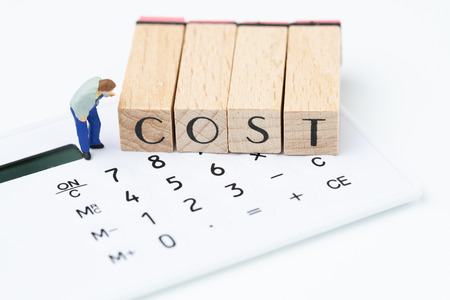 Photo pour Business costs and expense awareness, miniature figure, man carefully looking at wooden stamp block arrange the word COST on white calculator. - image libre de droit