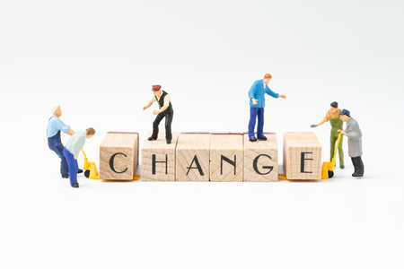 Foto de Business change, transform or self development for success concept, miniature people figure, workers, employee staffs help move wooden stamp block to arrange the word CHANGE on white background. - Imagen libre de derechos