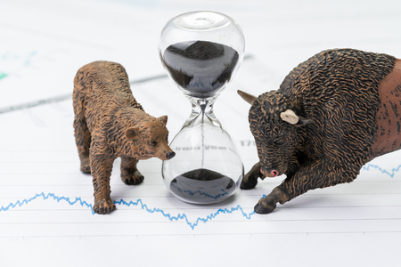 Photo pour Time counting down to choose between investment bear and bull stock market concept, hourglass or sandglass on chart and graph, price list report paper surround by bear and bull figure. - image libre de droit