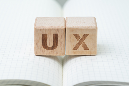 Foto de UX development, User Experience design concept, cube wooden block with alphabet U and X on grid line note book, user centric in modern world business, product and service. - Imagen libre de derechos
