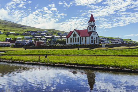 Foto de Amazing view of white church with red roof in beautiful sunshine in clouds sky and the reflection in the pond in front of the church next to the ocean, Sandavagur city in Vagar Island, Faroe Islands. - Imagen libre de derechos
