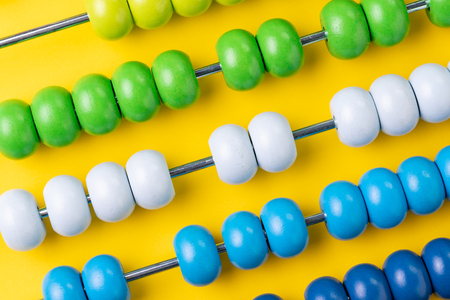 Foto de Colorful wooden abacus beads on yellow background, business financial or accounting profit and loss concept, or use in education school arithmetic symbol. - Imagen libre de derechos