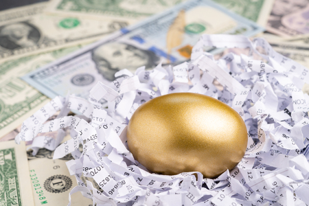 Foto de Closed up of golden egg in financial report shred paper with pile of US dollars banknotes using as lucky egg or valuable stock or success mutual funds in long term investment. - Imagen libre de derechos
