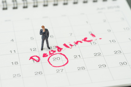 Foto de Miniature business man standing on desktop calendar with red circle on important date with handwriting deadline, goal or target date of work project plan, meeting or day of delivery. - Imagen libre de derechos