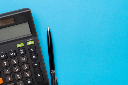 Foto per Financial activity, accounting, tax calculation or saving and investment, black calculator with pen on solid blue background with copy space. - Immagine Royalty Free