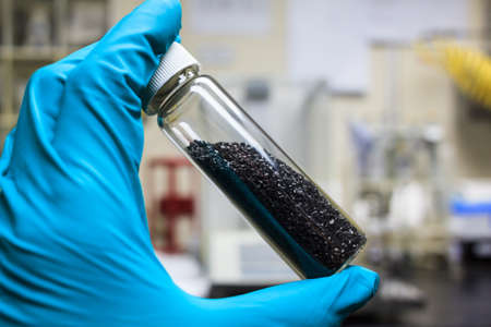 Foto de activated carbon charcoal coconut in clear bottom for use in laboratory, holding by green medical rubber hand glove. - Imagen libre de derechos