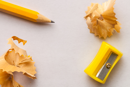 Photo pour Yellow pencil, sharpner and shavings on white paper background with copy space - image libre de droit