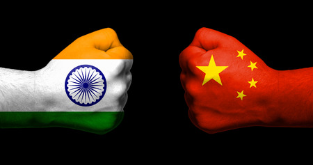 Foto de Flags of India and China painted on two clenched fists facing each other on black background/India - China relations concept - Imagen libre de derechos
