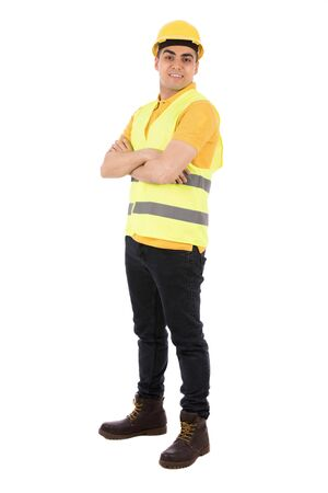 Photo for Full length shot of a happy young engineer smiling and holding and standing confidently, guy wearing yellow t-shirt and jeans with yellow vest and helmet, isolated on white background - Royalty Free Image