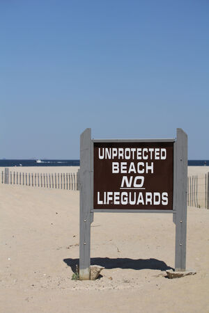 Photo for A sign reads  Unprotected Beach No Lifeguards   A clear blue sky is seen in the background along with a beach fence and ocean in the distance  Shallow depth of field - Royalty Free Image