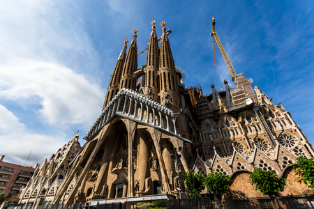 Foto de BARCELONA, SPAIN, June 8, 2017: Southwest view of the Sagrada Familia from Sardenya Street, lit by the afternoon sun. - Imagen libre de derechos
