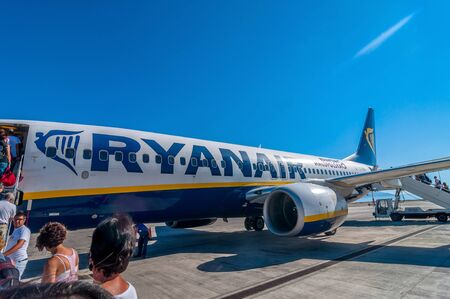 PALERMO, ITALY - AUGUST 27, 2014: passengers boarding Ryanair Jet airplane in Palermo airport, Italy. Ryanair is the biggest low-cost airline company in the world.