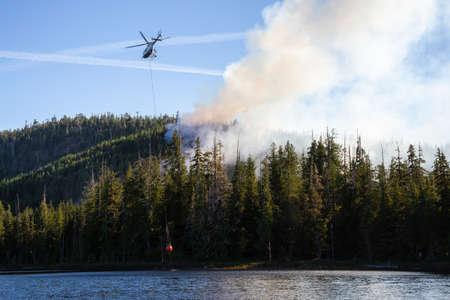 Foto de Helicopter fighting BC forest fires during a hot sunny summer day. Taken near Port Alice, Northern Vancouver Island, British Columbia, Canada. - Imagen libre de derechos