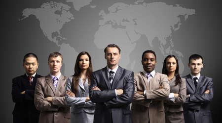 Foto de Businessmen standing in front of an earth map  - Imagen libre de derechos