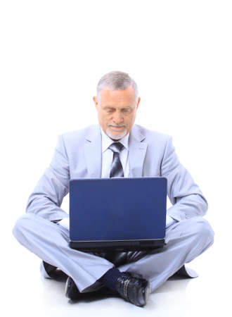 Executive sitting on the floor cross-legged with laptop
