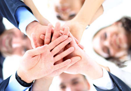 Foto de Small group of business people joining hands, low angle view. - Imagen libre de derechos