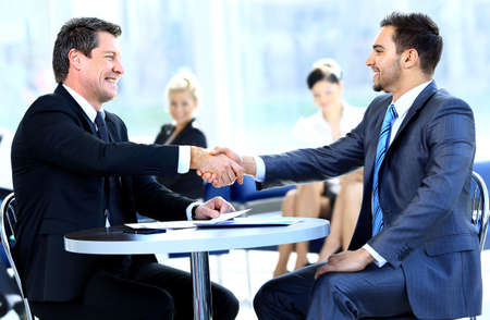 Foto de Two business colleagues shaking hands during meeting - Imagen libre de derechos