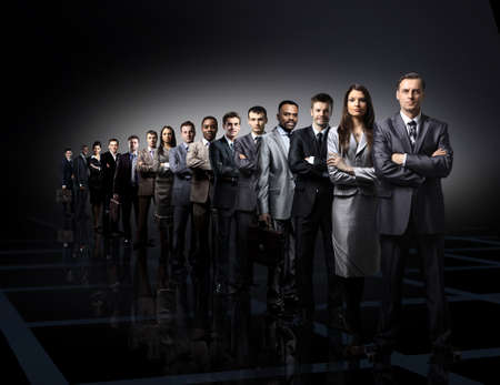 Foto de business team formed of young businessmen standing over a dark background - Imagen libre de derechos