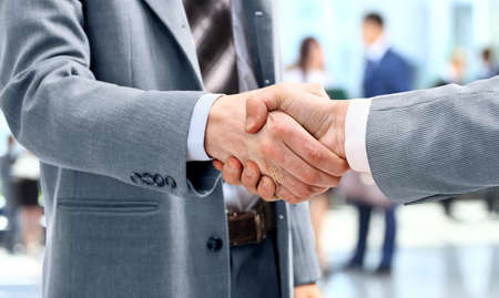 Photo pour Handshake in front of business people - image libre de droit