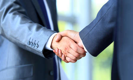 Photo pour Two businessman shaking hands - image libre de droit