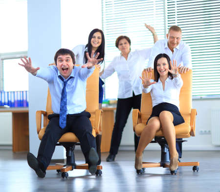 Photo for Happy office employees having fun at work in an office chair race - Royalty Free Image