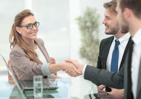 Photo pour Happy smiling business people shaking hands after a deal in offi - image libre de droit