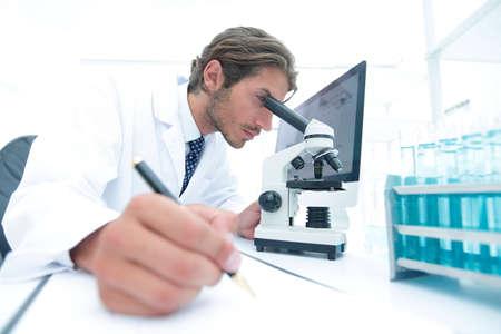 Foto de scientist makes a note of experiment in the laboratory - Imagen libre de derechos