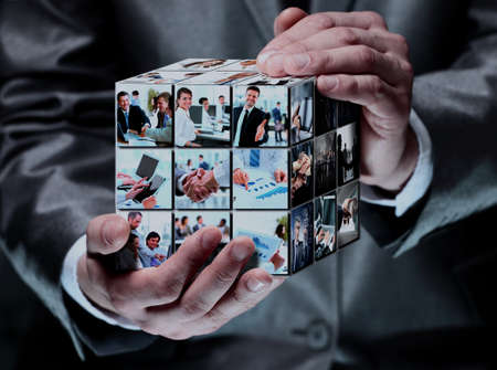 Photo pour man holding abstract cube with business images - image libre de droit