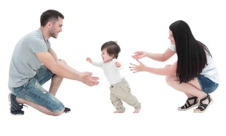 Foto de little boy making  first steps with the help of parents - Imagen libre de derechos