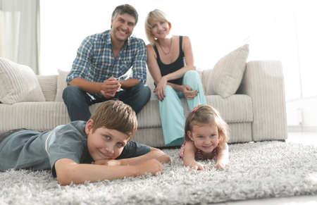 Photo pour Portrait of happy family sitting together in living room - image libre de droit