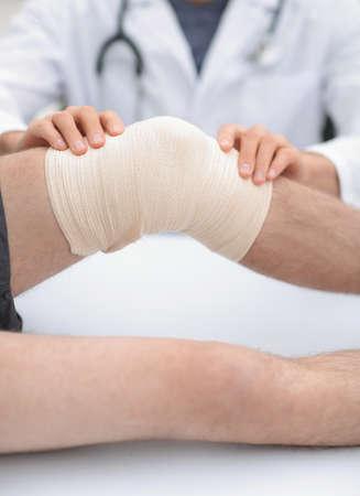 Photo pour traumatologist ,applying a bandage on the knee - image libre de droit