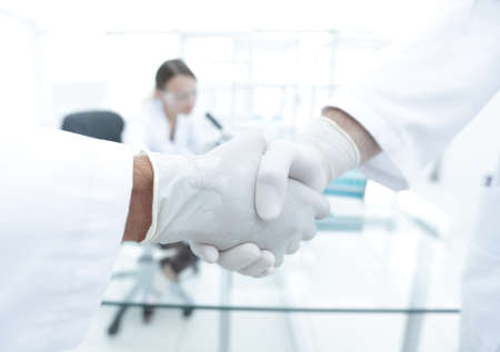 Photo for Doctors in lab coats greeting each other with handshake - Royalty Free Image