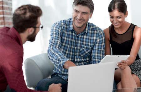 Foto de Business colleagues discussing on report with laptop on table - Imagen libre de derechos