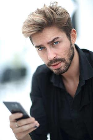 Foto de A stylish bearded male sits and uses a smartphone. - Imagen libre de derechos