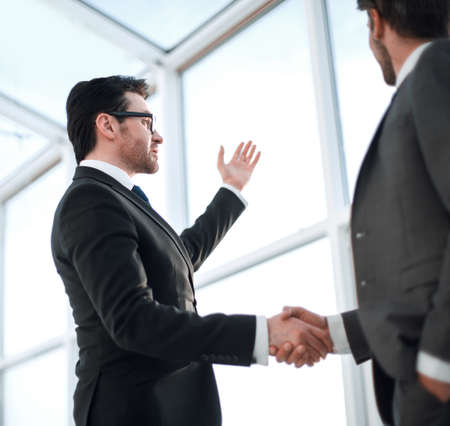 Photo for close up of a businessmen shaking hands during a conversation in the office - Royalty Free Image