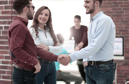 Photo for Smiling businessman shaking hands with colleague in office. - Royalty Free Image