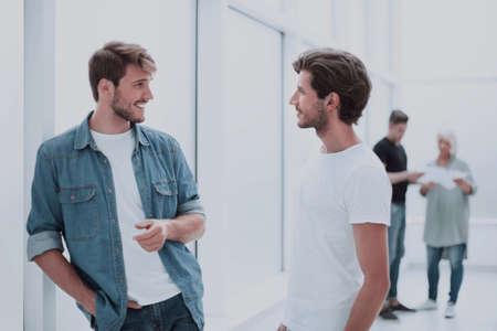 Foto de two colleagues talking standing in the office corridor - Imagen libre de derechos