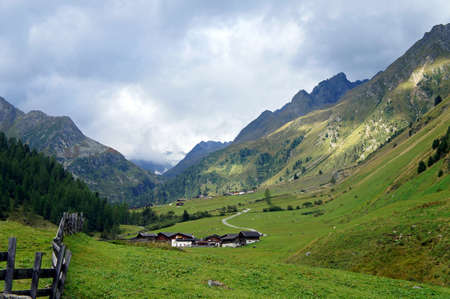 Landscape in the Stubai Valley in Tyrol, Austria, mountains, partial in clouds, alpine pastures, steep rocks, green meadows, cloudy sky