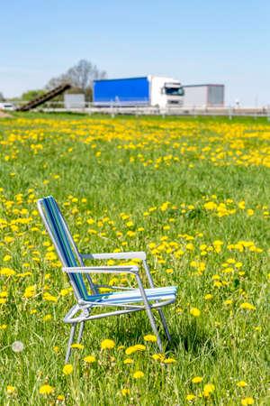 Photo pour Abandoned garden chair in flower meadow - image libre de droit