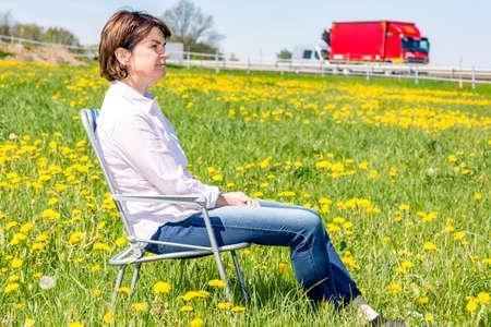 Photo pour Woman sitting on garden chair in a flower meadow - image libre de droit