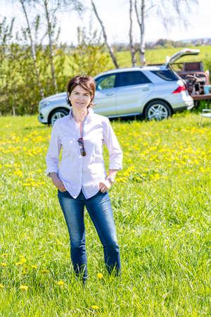 Photo pour Middle-aged woman running over flower meadow - image libre de droit