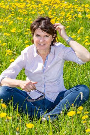 Photo pour Middle-aged woman sitting in a flower meadow  - image libre de droit