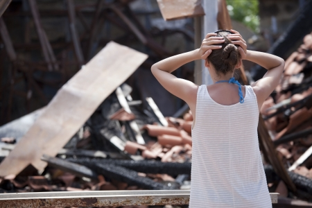 woman standing in front of burned out house and holding her head with both hands