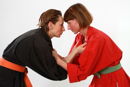 two women in judo kimonos in fighting stance over white background